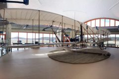 A model of the Wright Flyer with preserved artifacts from the original aircraft displayed around it